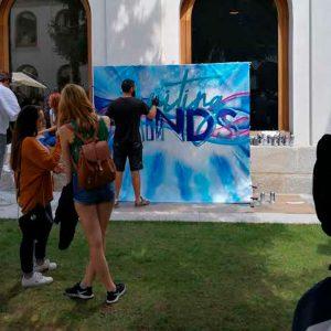 Grafitero pintando en directo en evento de universidad.