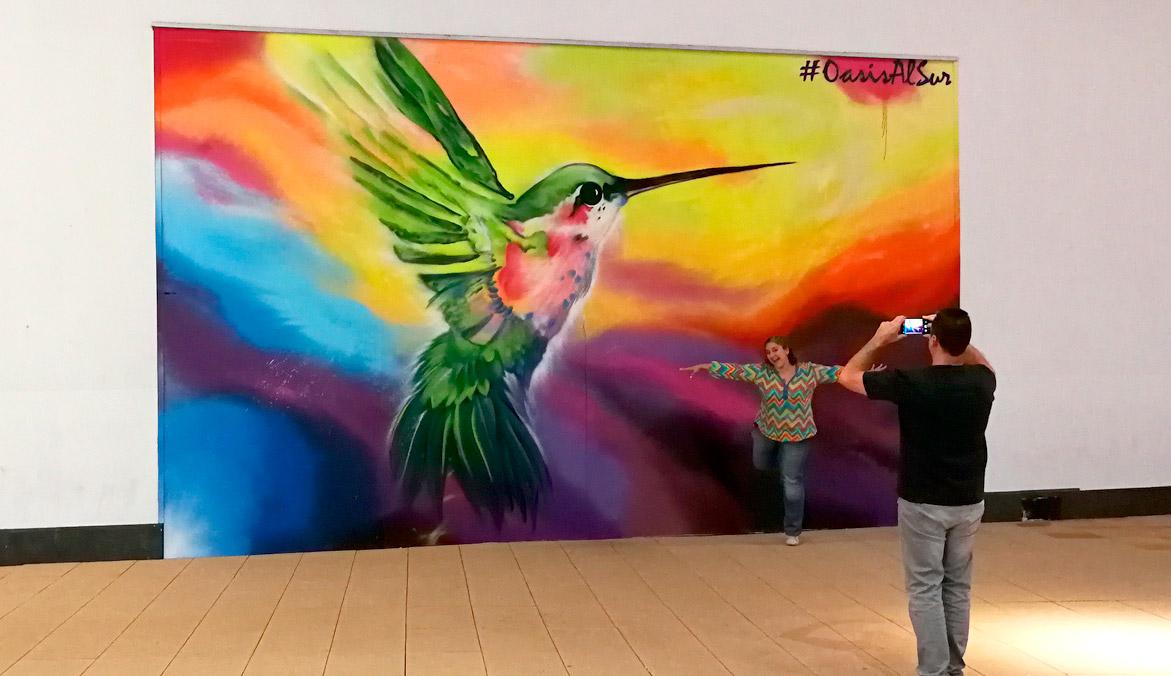 Asistentes haciéndose fotos en el evento con el graffiti.